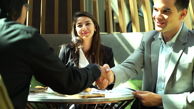business people handshaking demonstrating their agreement to sign agreement or contract between their firms / companies / enterprises. - finishing stock videos & royalty-free footage