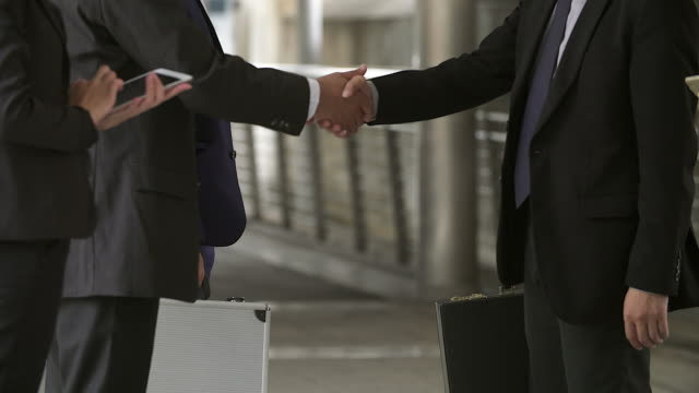 business people handshaking demonstrating their agreement to sign agreement or contract between their firms / companies / enterprises. - trust stock videos & royalty-free footage