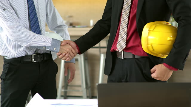 Business people handshaking demonstrating their agreement to sign agreement or contract between their firms / companies / enterprises.