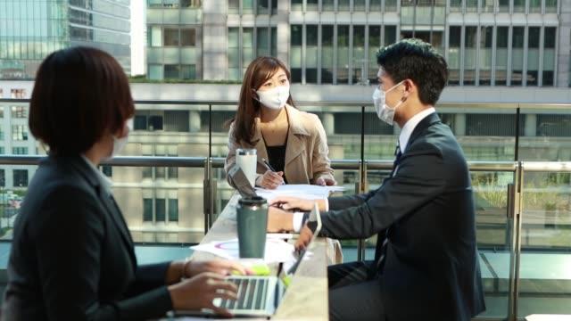 ビジネスの人々は、アジアで保護マスクを着用して社会的な離散との会合を持っています - 動画関連点の映像素材/bロール