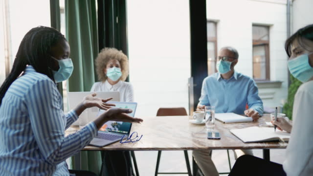 business people having a meeting during the coronavirus pandemic - small group of people stock videos & royalty-free footage