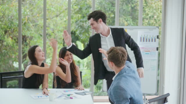 Business people high-fiving in office,Slow motion