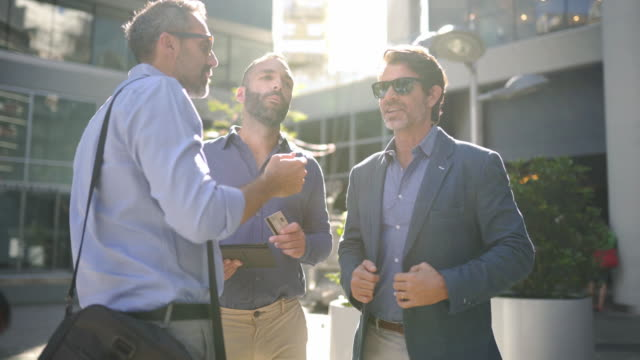 business people in front of business building on break after work - handsome people stock videos & royalty-free footage