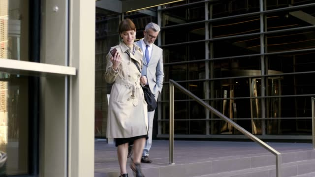 business people leaving office building - coworker stock videos & royalty-free footage