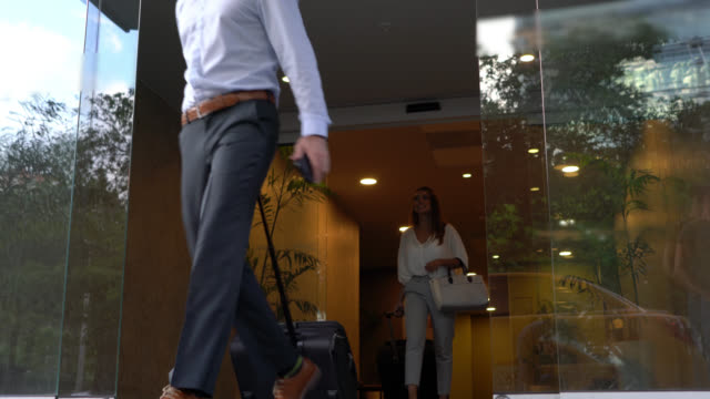 business people leaving the hotel with their wheeled luggage looking very happy - wheeled luggage stock videos & royalty-free footage