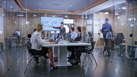 ds business folk lyssnar på deras asiatiska kollega håller en presentation i glas konferensrummet - planering bildbanksvideor och videomaterial från bakom kulisserna