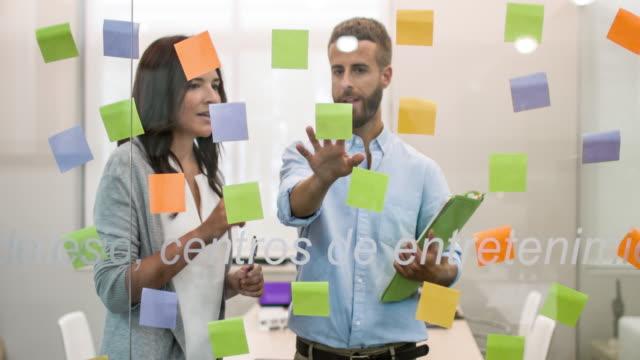 Mensen uit het bedrijfsleven kijken zelfklevende notities in vergaderruimte