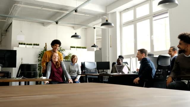 vidéos et rushes de collègues s'amuser en regardant les gens d'affaires - chaise de bureau