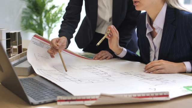 ディスカッションのための会話を持つラップトップを見ているビジネスの人々 - 設計図点の映像素材/bロール