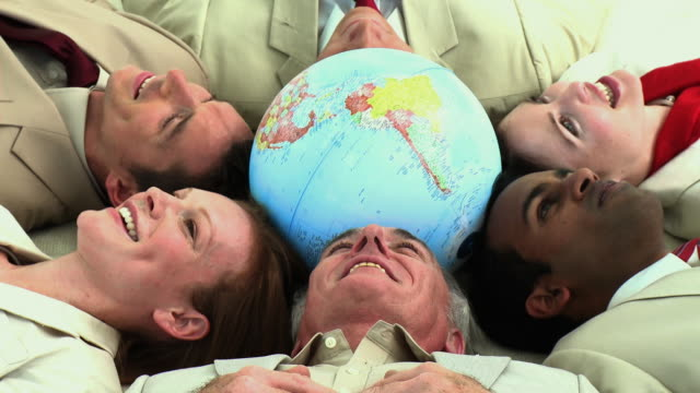 vídeos de stock e filmes b-roll de cu business people lying on back touching globe with heads / cape town, south africa - globo terrestre de escritório