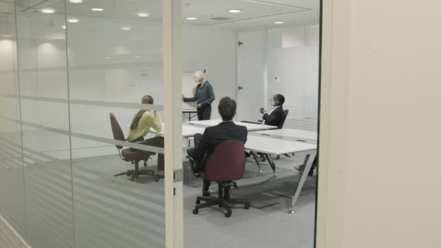 business people meeting in boardroom wearing protective face mask for presentation - formal businesswear stock videos & royalty-free footage