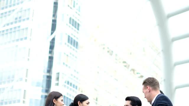 uomini d'affari che si incontrano nel centro della capitale, stanno tutti parlando nel central business district - abbigliamento da lavoro formale video stock e b–roll
