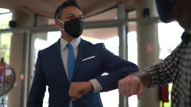 business people on a safety greeting for covid-19 on office's lobby - with face mask - greeting stock videos & royalty-free footage