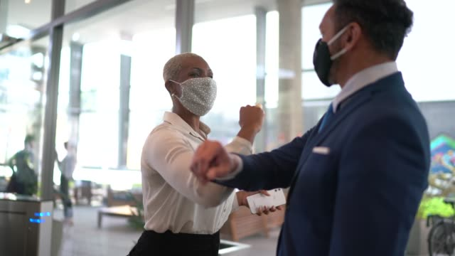 business people on a safety greeting for covid-19 on office's lobby - with face mask - arrival stock videos & royalty-free footage