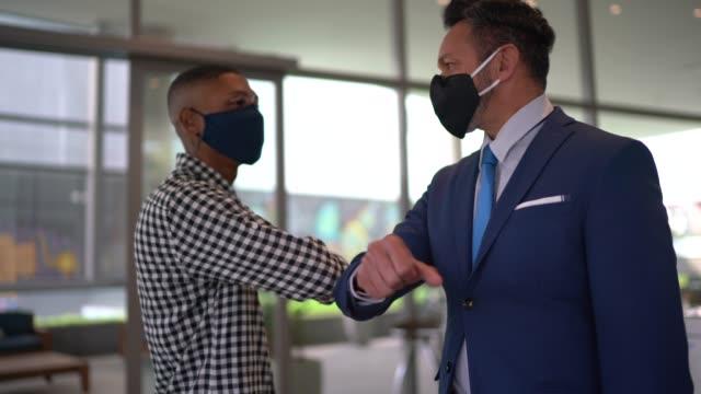 vídeos y material grabado en eventos de stock de empresarios en un saludo de seguridad para covid-19 en el vestíbulo de la oficina - con máscara facial - codo