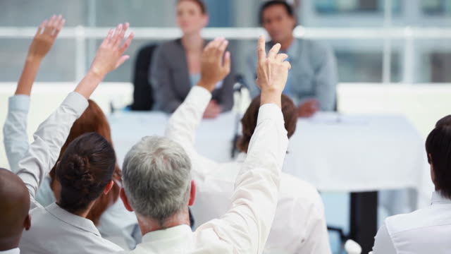 business people raising their hands to ask questions - arms raised stock videos and b-roll footage
