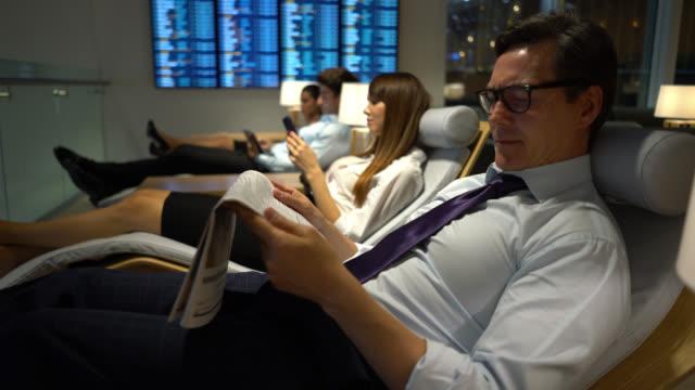 vidéos et rushes de personnes d'affaires détendant au salon vip d'aéroport - première classe