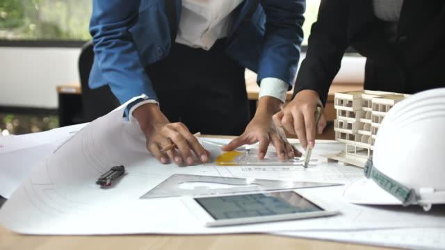 vídeos y material grabado en eventos de stock de las personas de negocios de revisar blueprints en escritorio - cianotipo plano