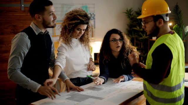 ビジネスの人々のデスクでの設計図をレビューする - コミュニケーション点の映像素材/bロール