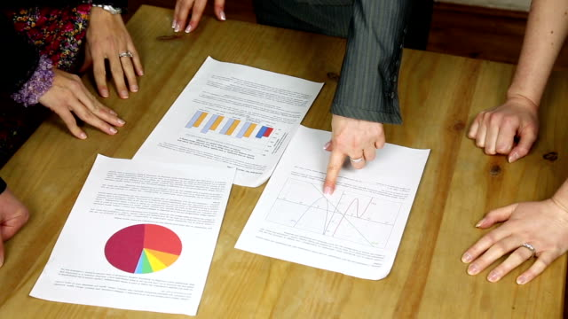business people sat around table discussing performance graphs and statistics - file stock videos & royalty-free footage