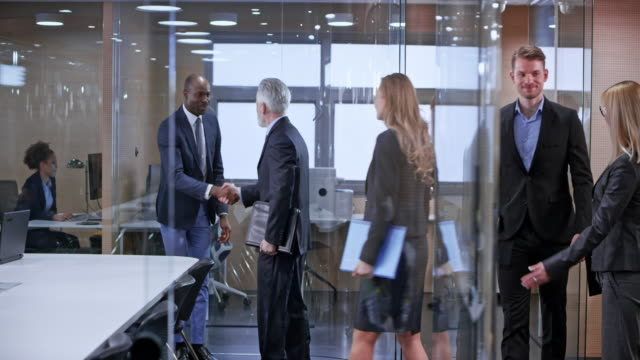 ds business people shaking hands in the glass conference room upon arrival - customer stock videos & royalty-free footage