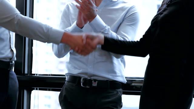 握手ビジネス人々 他のビジネス人々 の良い仕事のための明るいオフィスで拍手をしながら。 - 決意点の映像素材/bロール