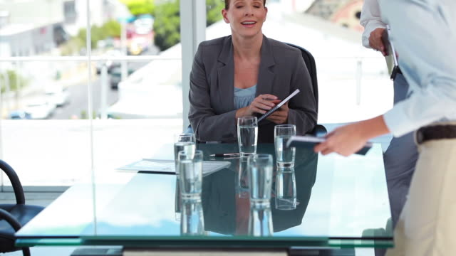 business people sitting at a table - mitarbeiterengagement stock-videos und b-roll-filmmaterial