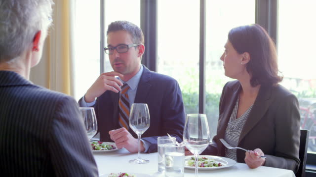 MS business people sitting in discussion during lunch meeting at table in restaurant.