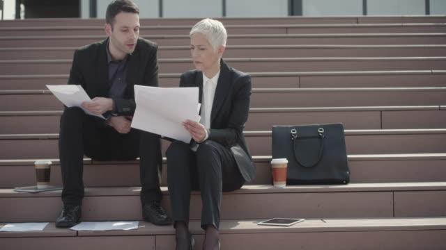 vidéos et rushes de 4 k : gens d'affaires assis sur l'escalier et regardant les documents. - serbie