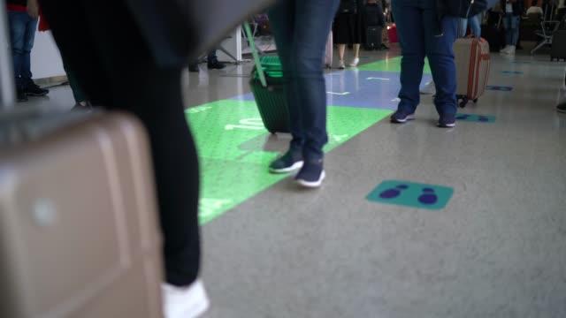 vídeos de stock, filmes e b-roll de empresários que estão atrás da sinalização de distanciamento social no chão do aeroporto - travel destinations