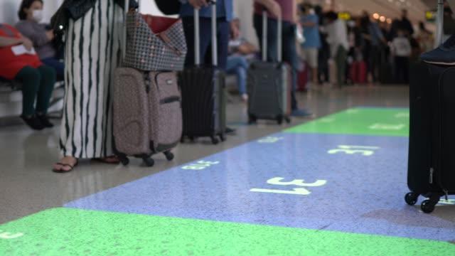 vídeos de stock, filmes e b-roll de empresários que estão atrás da sinalização de distanciamento social no chão do aeroporto - passageiro