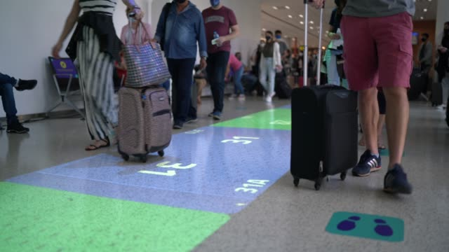 business people standing behind social distancing signage on airport floor - distant stock videos & royalty-free footage