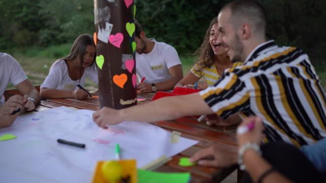 geschäftsleute kleben herzförmige klebeschnoten mit ihren namen während des informellen unterrichts - vortrag stock-videos und b-roll-filmmaterial