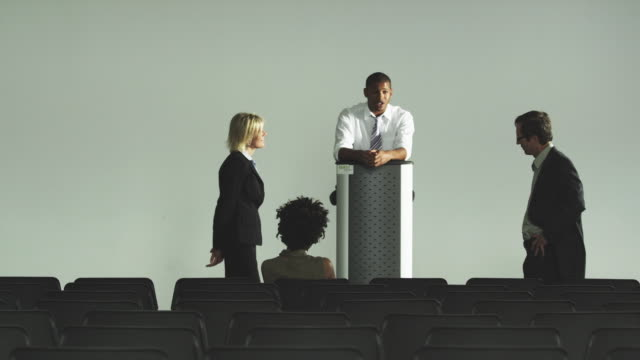 WS DS Business people talking by lectern in auditorium, Squamish, British Columbia, Canada