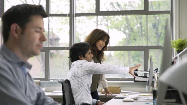 Business people talking in office near computer