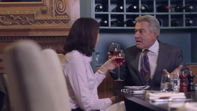 ms business people talking in restaurant, waiter serving wine - 全套西裝 個影片檔及 b 捲影像