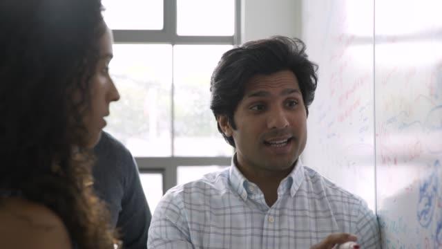 business people talking near whiteboard in meeting - whiteboard stock videos & royalty-free footage