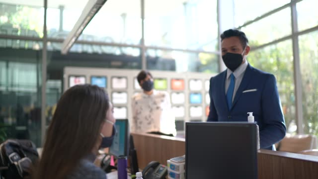 business people talking to receptionist on entrance of office's lobby - with face mask - building entrance stock videos & royalty-free footage