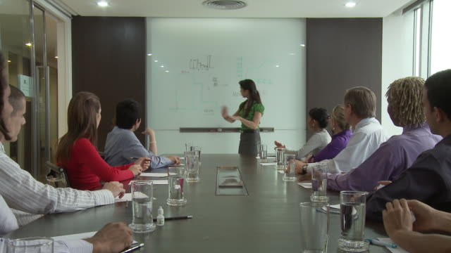 WS Business people throwing paper balls at business woman speaking in front of whiteboard in conference room / Bangkok, Thailand