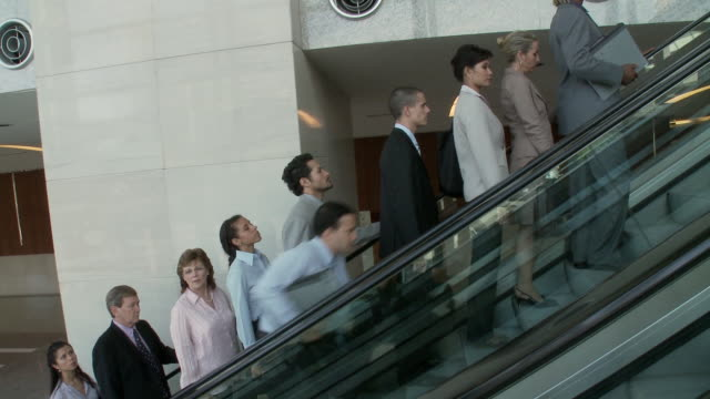 ms ts business people traveling on escalator, man running past / bangkok, thailand - anzug stock-videos und b-roll-filmmaterial