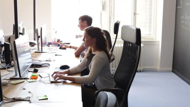 geschäftsleute, die computer im büro - kreativer beruf stock-videos und b-roll-filmmaterial