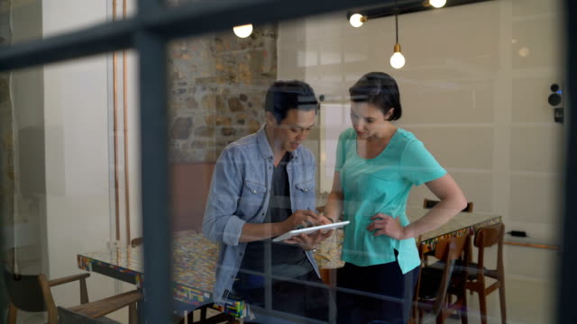 vídeos de stock, filmes e b-roll de business people using digital tablet in board room - touch screen