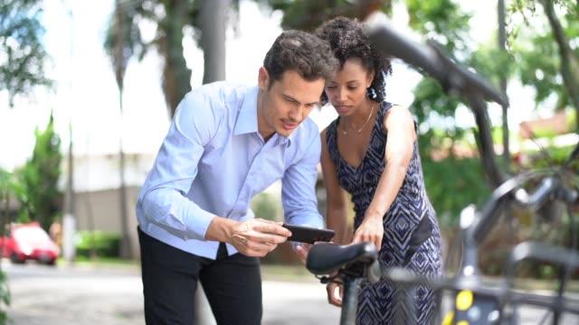 vídeos de stock e filmes b-roll de business people using smartphone scanning the qr code of shared bike in city - a caminho