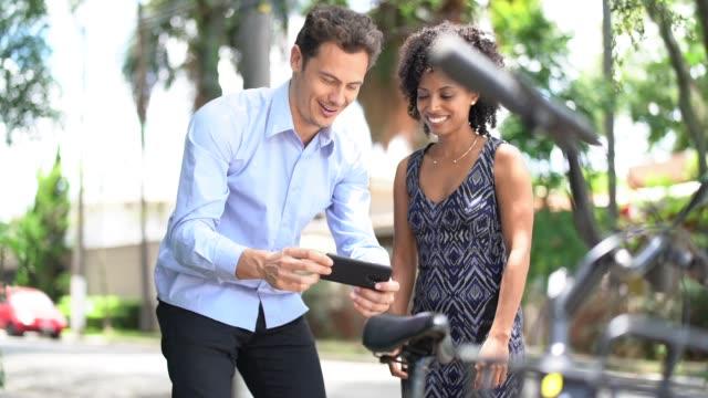 vídeos de stock, filmes e b-roll de pessoas de negócios usando smartphone digitalizar o código qr de bicicleta compartilhada na cidade - dividir
