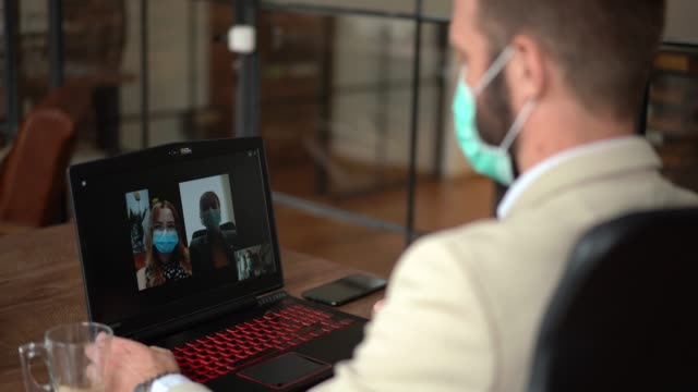 business people video conferencing during covid-19 pandemic - outsourcing stock videos & royalty-free footage
