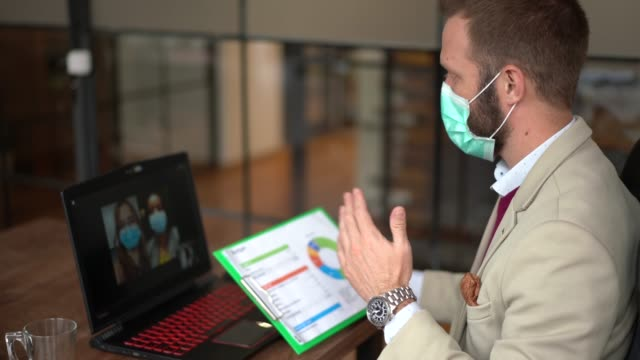 business people video conferencing during covid-19 pandemic - pollution mask stock videos & royalty-free footage