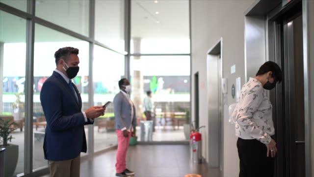 vidéos et rushes de gens d'affaires marchant et entrant à l'ascenseur avec le masque de visage au bureau de hall - collègue de bureau