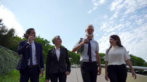 stockvideo's en b-roll-footage met bedrijfsmensen die en in een openbaar park na het werk lopen ontspannen - after work