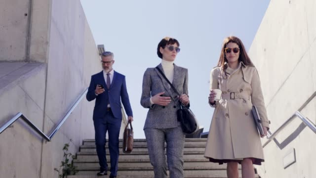 business people walking down stairs on sunny day - sunglasses stock videos & royalty-free footage