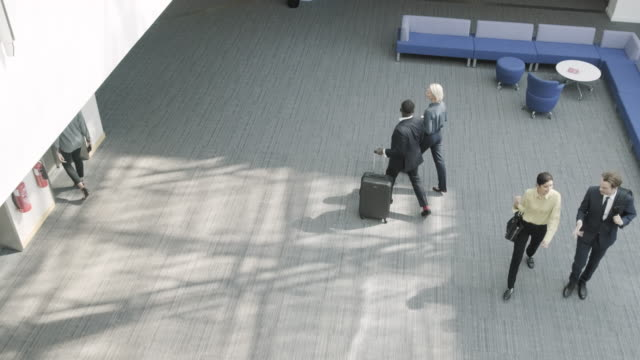 business people walking in airport terminal lounge and checking departure time on smart watch - geschäftsreise stock-videos und b-roll-filmmaterial